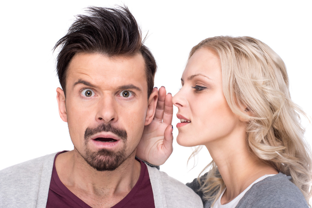 Amazed man is listening gossip in the ear from woman on the white background.